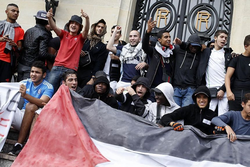 Protestors hold a Palestinian flag as they take part in a demonstration on July 22, 2014 to denounce Israel's military campaign in Gaza and to show their support to the Palestinian people in Aulnay-sous-Bois, north suburb of Paris. -- PHOTO: AFP&nbsp