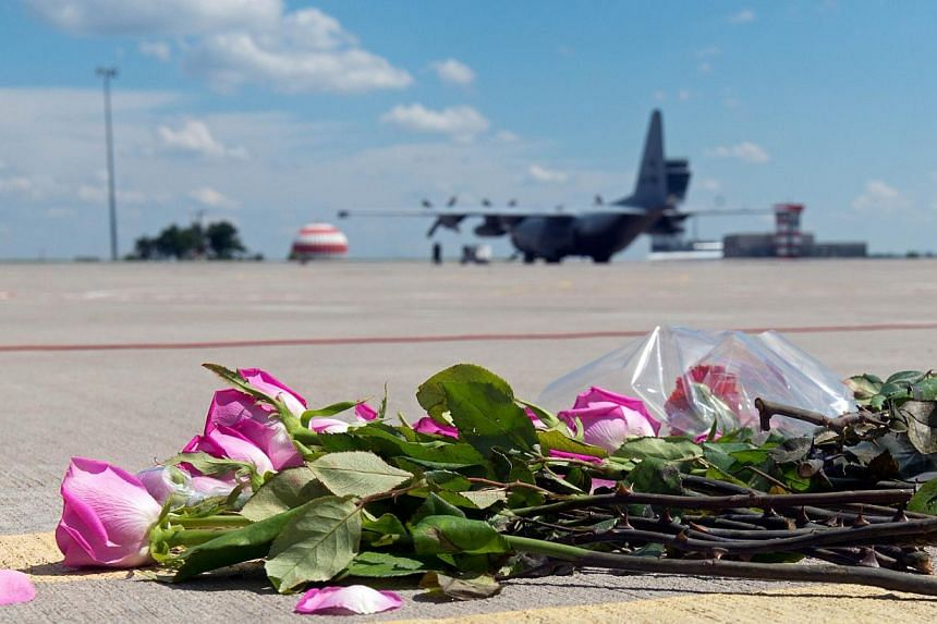 Flowers lay on the tarmac as a ground Hercules transport aircraft of the Royal Dutch Airforce, carrying bodies from downed Malaysia Airlines Flight MH17, prepares to take off from Kharkiv airport on July 23, 2014.Two aircraft carrying the remai