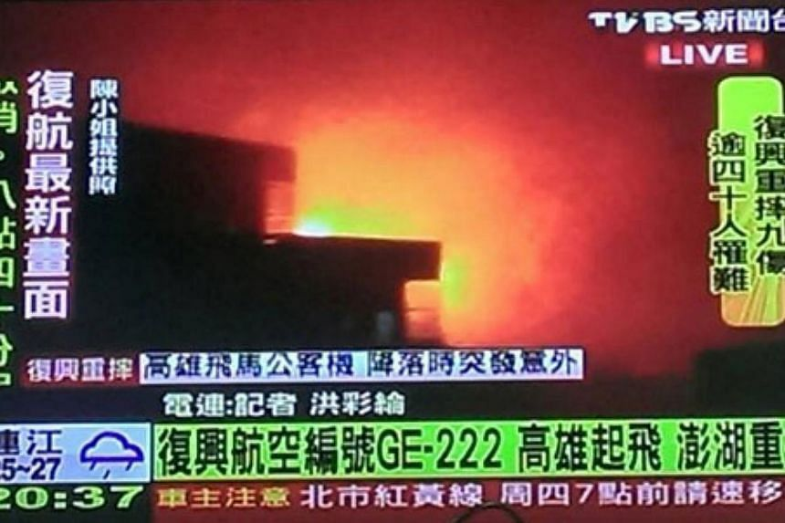 A screengrab from a TVBS report, after a TransAsia Airways plane carrying 58 people from Taiwan's Kaohsiung crashed into two houses, killing dozens of people. -- PHOTO: TVBS