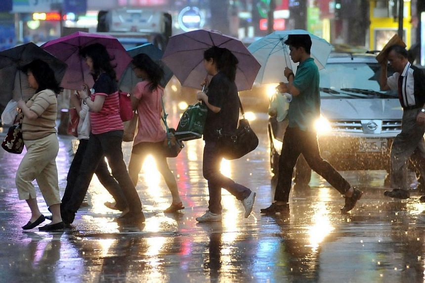 Pedestrians shield themselves from the rain with umbrellas as they cross a street in Taipei on July 22, 2014 as Typhoon Matmo approaches eastern Taiwan. -- PHOTO: AFP