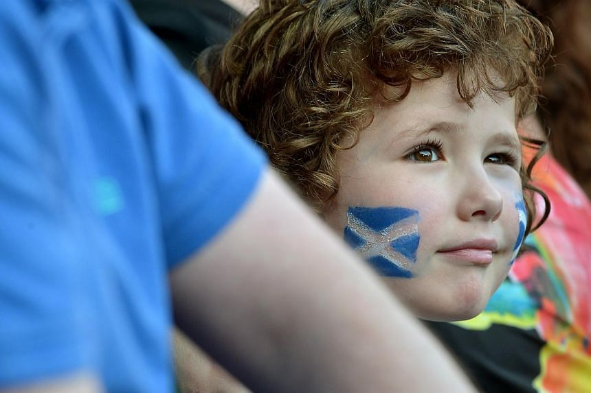 A boy watches the opening ceremony of the 2014 Commonwealth Games at Celtic Park in Glasgow on July 23, 2014. -- ST PHOTO: KUA CHEE SIONG