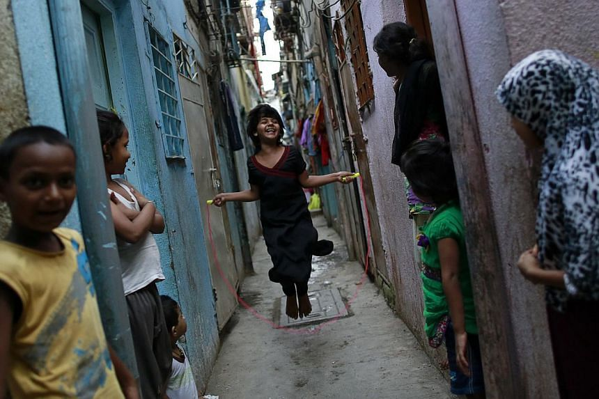 A girl jumps rope in an alley as others watch in Dharavi, one of Asia's largest slums, in Mumbai -- PHOTO: REUTERS