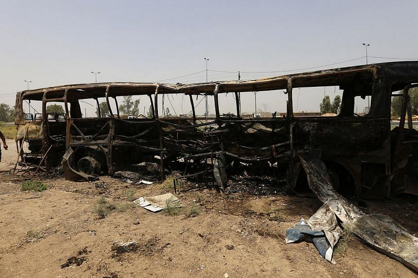 A man walks past a burnt bus in Taji, north of Baghdad on Thursday, July 24, 2014. An onslaught on a convoy transferring inmates north of Baghdad left dozens dead on Thursday, as visiting UN chief Ban Ki Moon said Iraq's survival hinged on