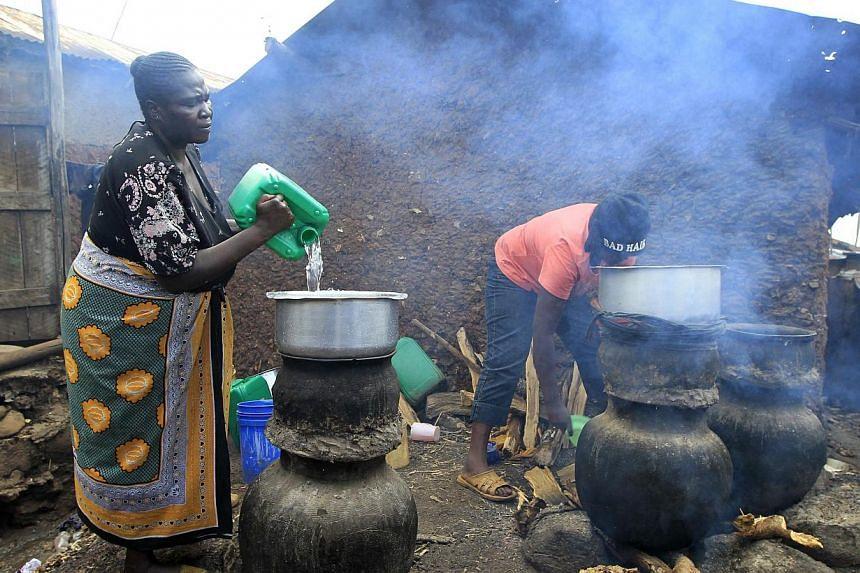 "Mama Jane Adhiambo prepares distilled traditional brewed alcoholic liquor, locally known as ""chang'aa"", at an illegal micro-brewery in Kibera slum in the suburbs of Kenya's capital Nairobi May 11, 2014 -- PHOTO: REUTERS"