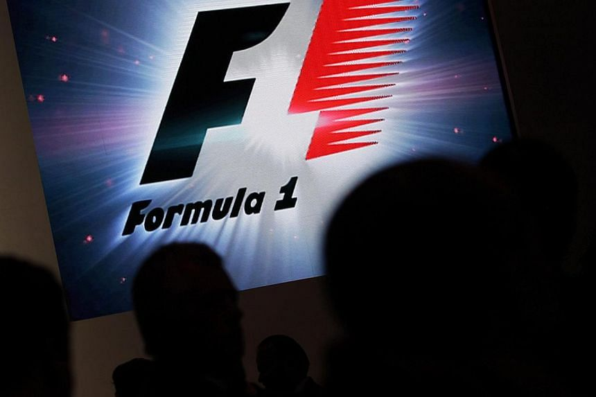 Reporters are silhouetted by a screen showing a F1 logo during a news conference to announce a Formula One race in Mexico City on July 23, 2014. -- PHOTO: REUTERS