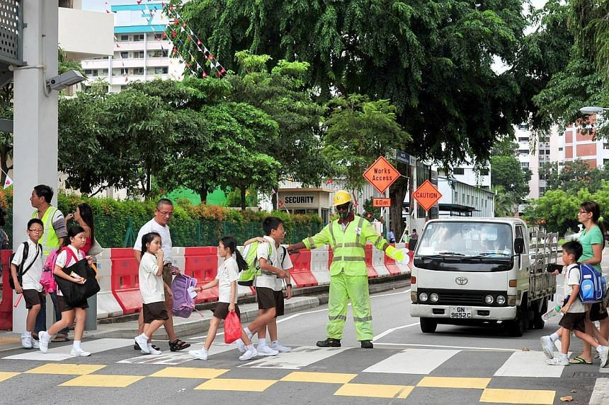 A traffic marshal directing a lorry along the special access road off the Central Expressway. A traffic marshal guiding pupils from Hong Wen School across a zebra crossing. Singapore Power has taken various safety measures, including deploying traffi