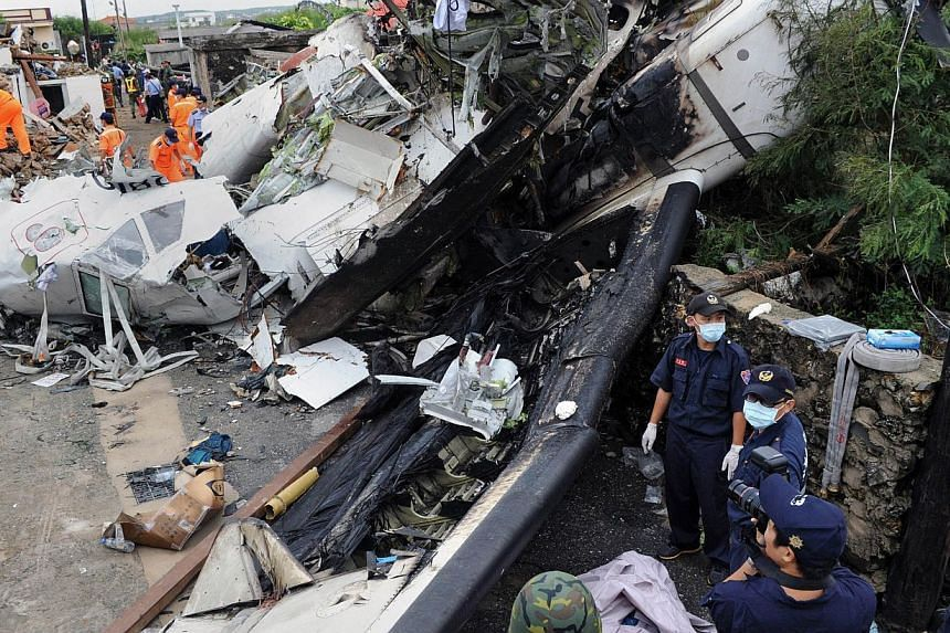 Rescue workers and firefighters search through the wreckage where TransAsia Airways Flight GE222 crashed the night before near the airport at Magong on the Penghu island chain on July 24, 2014. -- PHOTO: AFP
