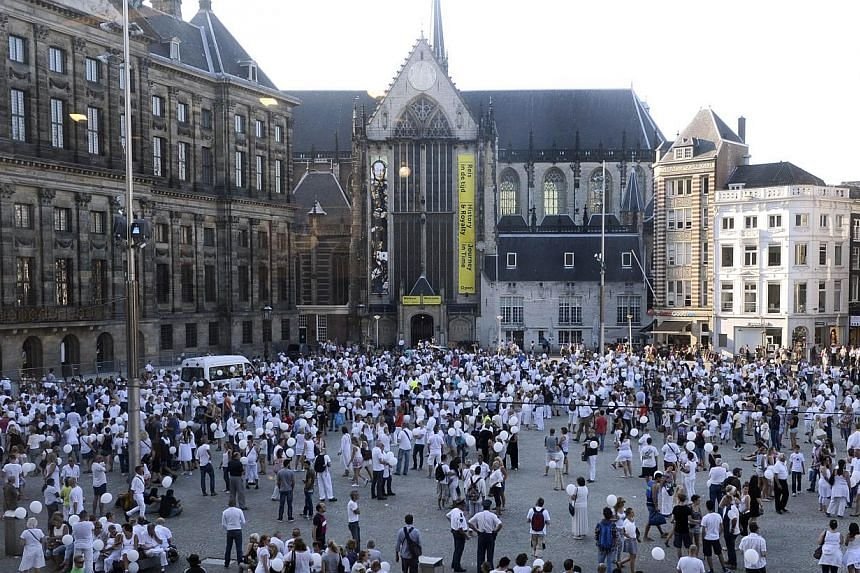 People wearing white clothes gather on Dam Square in Amsterdam, during a silent march in memory of the victims of the downed Malaysia Airlines flight MH17, on July 23, 2014. -- PHOTO: AFP