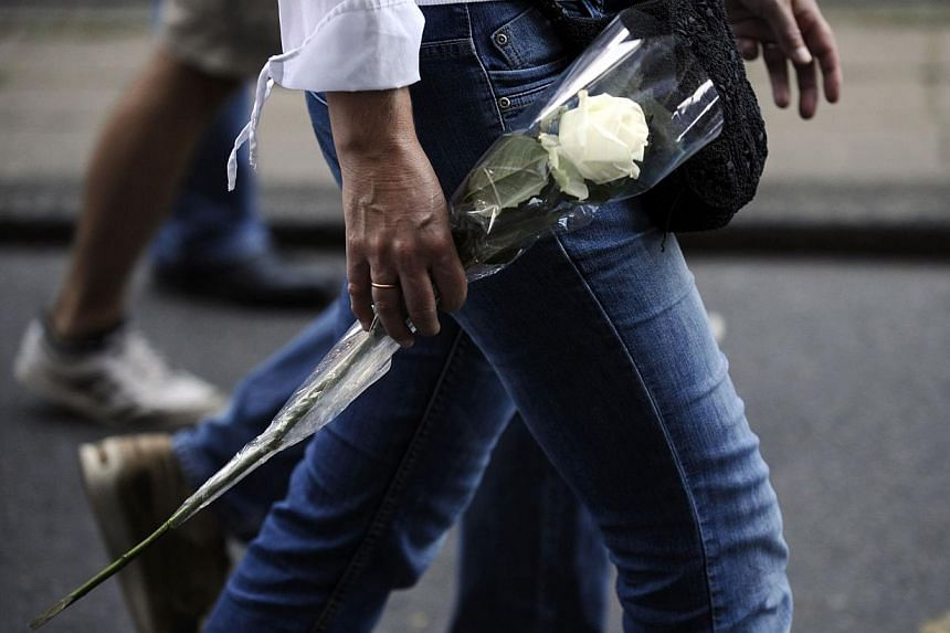 A person holds a white rose during a silent march in memory of the victims of the downed Malaysia Airlines flight MH17, in Amsterdam on July 23, 2014. -- PHOTO: AFP