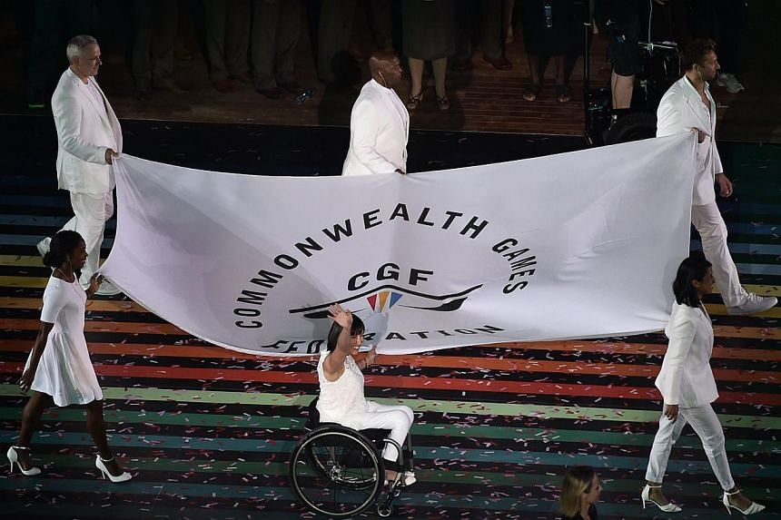 Flagbearers of the Commonwealth Games Federation display the flag during the opening ceremony of the 2014 Commonwealth Games at Celtic Park in Glasgow on July 23, 2014. -- PHOTO: AFP
