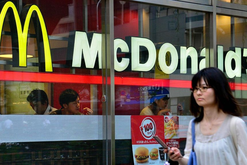A pedestrian passes before a McDonald's restaurant in Tokyo on July 23, 2014. -- PHOTO: AFP