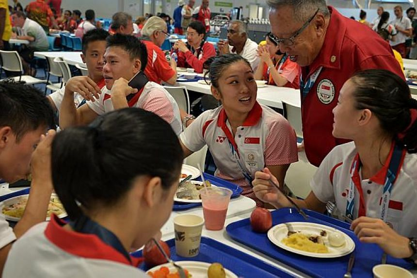 Commonwealth Games flag-bearer Lim Heem Wei speaks with the chef de mission Low Teo Ping at the cafeteria of the Games Village. -- ST PHOTO: KUA CHEE SIONG