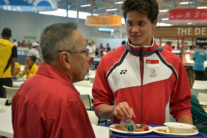 Joseph Schooling speaks with chef de mission Low Teo Ping at the cafeteria of the games village.  -- ST PHOTO: KUA CHEE SIONG
