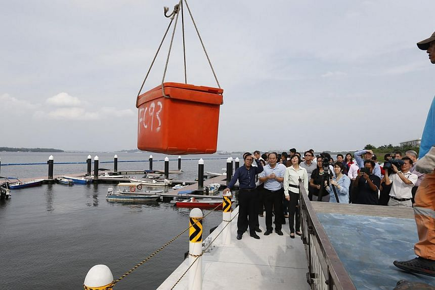 A box of fresh fish is unloaded during the official opening of Lorong Halus Jetty at 50 Pasir Ris Coast Industrial Park 6 on 24 July 2014.To boost Singapore's sustainable food fish production, the Agri-Food and Veterinary Authority (AVA) is com