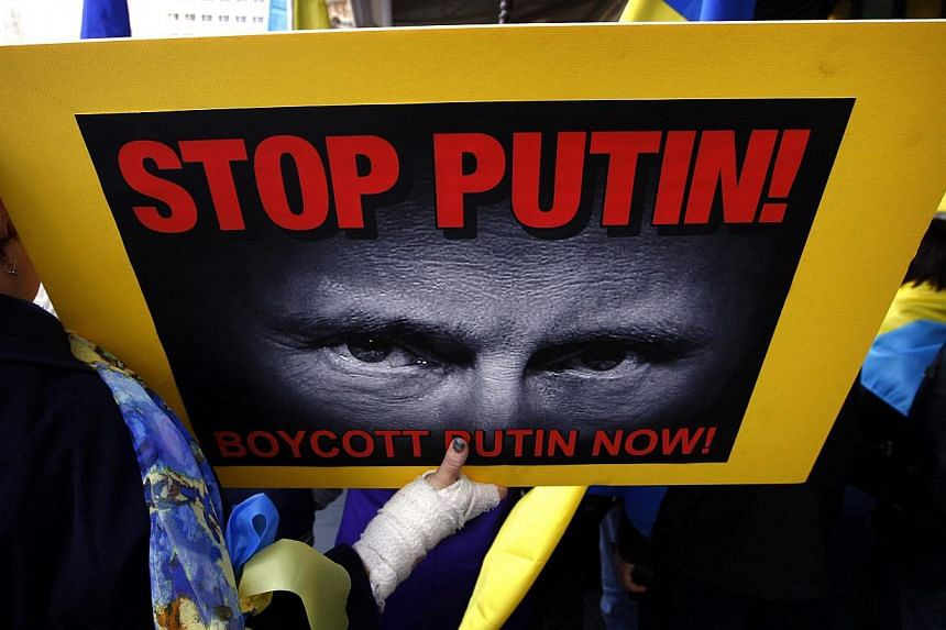 Members of the Australian Ukrainian community hold placards as they hold a rally in Sydney on July 19, 2014, demanding that Russian President Vladimir Putin not be allowed to attend the G20 Leaders Summit in November. -- PHOTO: REUTERS