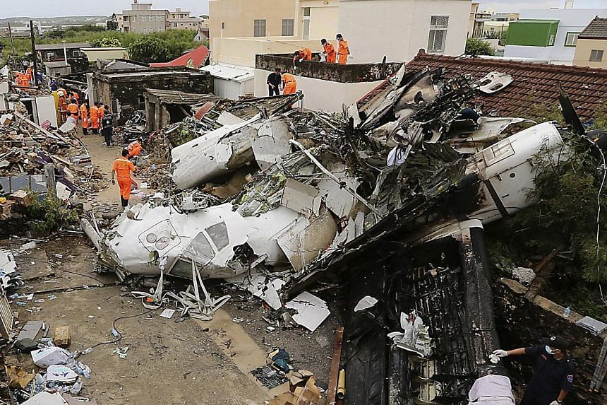 Rescue personnel survey the wreckage of a TransAsia Airways turboprop plane that crashed, on Taiwan's offshore island Penghu on July 24, 2014. -- PHOTO: REUTERS