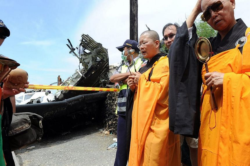 Buddhist monks pray for the passengers on TransAsia Airways flight GE222 the day after the ATR 72-500 plane crashed near the airport at Magong on the Penghu island chain on July 24, 2014. -- PHOTO: AFP