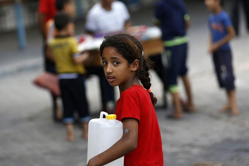 A displaced Palestinian girl carries a fresh water jerrycan at a school used as a shelter in Gaza City on July 18, 2014. -- PHOTO: AFP