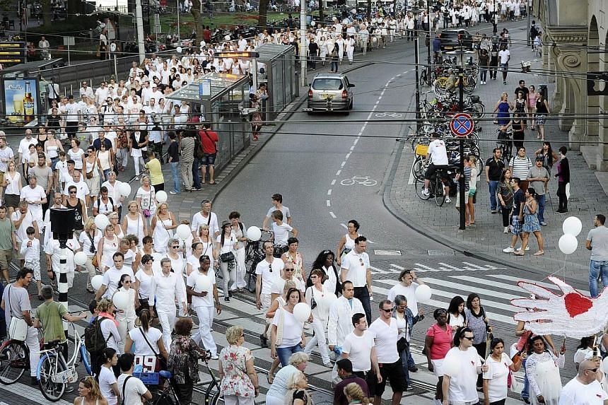 People take part in a silent march in memory of the victims of the downed Malaysia Airlines flight MH17, in Amsterdam on July 23, 2014. -- PHOTO: AFP