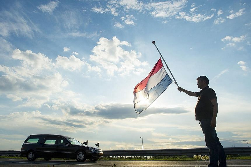 Dutch Ronald Visee holds a Netherlands flag flying at half-mast (right) as a hearse carrying the remains of victims of the Malaysia Airlines flight MH17 plane disaster are escorted on highway A27 near Nieuwegein by military police, on their way to be