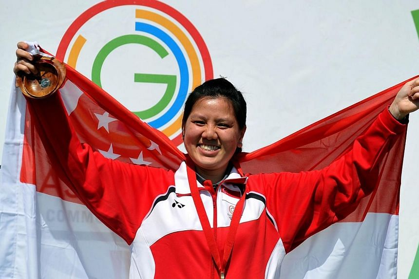 Teo Shun Xie of Singapore celebrates winning the 10m Air Pistol event at the Barry Buddon Shooting Centre in Carnoustie, Scotland on July 25, 2014, during the 2014 Commonwealth Games. -- PHOTO: AFP