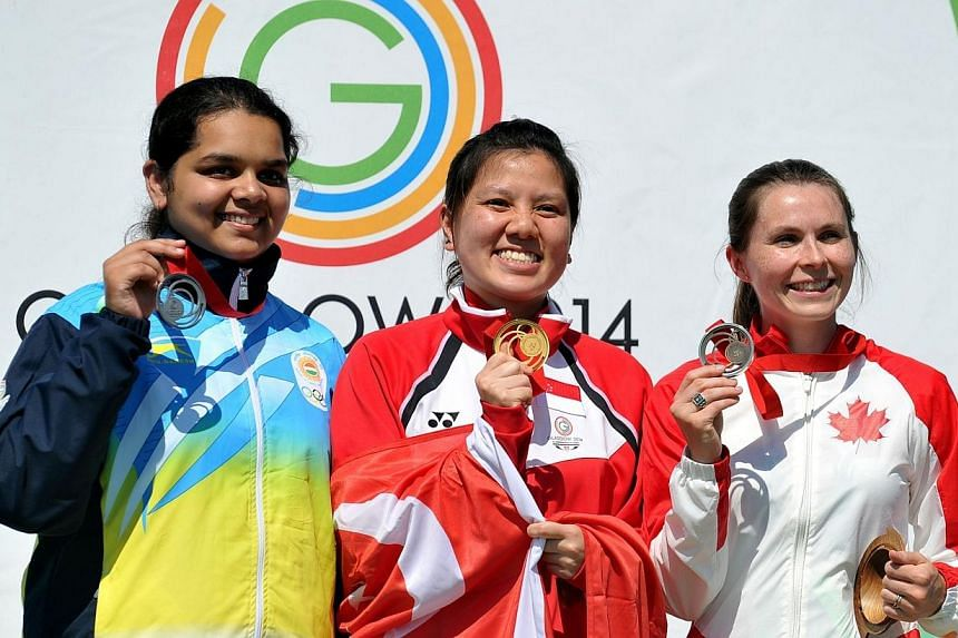 (From left) Malaika Goel of India, Teo Shun Xie of Singapore and Dorothy Ludwig of Canada pose with their medals after the 10m Air Pistol event at the Barry Buddon Shooting Centre in Carnoustie, Scotland on July 25, 2014, during the 2014 Commonwealth