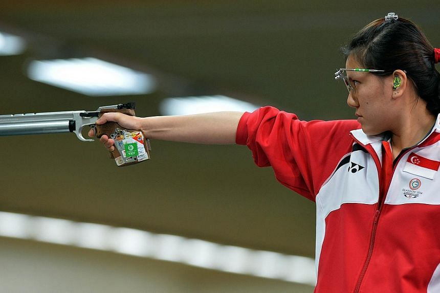 Teo Shun Xie of Singapore shoots during the 10m Air Pistol event at the Barry Buddon Shooting Centre in Carnoustie, Scotland on July 25, 2014, during the 2014 Commonwealth Games. -- PHOTO: AFP