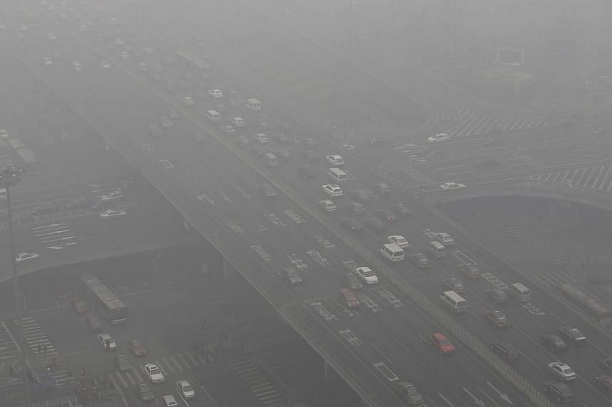 Vehicles drive through the Guomao Bridge on a heavy haze day in Beijing's central business district on Jan 29, 2013.China's overgrown and smog-hit capital has passed new rules banning the expansion of polluting and resource-intensive industries