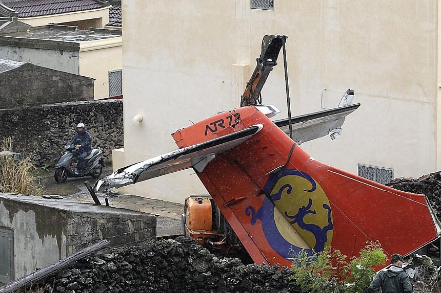 Soldiers remove the wreckage of a TransAsia Airways turboprop plane that crashed on the rooftop, on Taiwan's offshore island Penghu on July 25, 2014. Taiwan's TransAsia Airways ran an apology on the front pages of five major newspapers on Friday