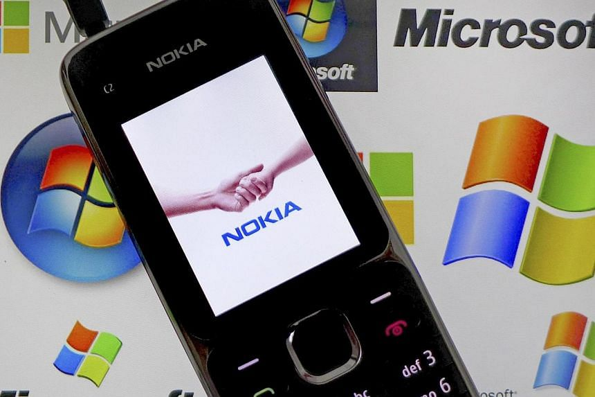 A Nokia mobile phone lies on a tablet computer showing logos of Microsoft, in this illustration photo taken in Frankfurt on Nov 18, 2013. -- PHOTO: REUTERS