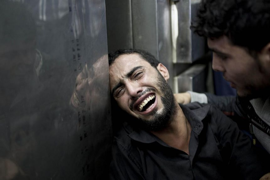 A Palestinian man grieves over the death of his relatives at the morgue of the Kamal Adwan hospital in Beit Lahiya on July 24, 2014, after a UN school in the northern Beit Hanun district of the Gaza Strip was hit by an Israeli shell. -- PHOTO: AFP
