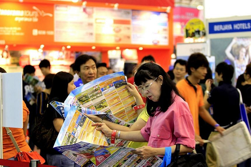 A woman looks through a tour brochure at the Natas Travel 2014 fair held at Singapore Expo in Changi on 1 March 2014. The MH17 plane crash has not deterred Singaporeans from visiting Europe, though some have been checking with travel agents to make s