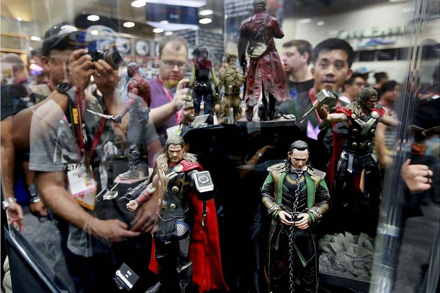Comic fans look at character dolls from Thor during the 2014 Comic-Con International Convention in San Diego, California on July 24, 2014. -- PHOTO: REUTERS