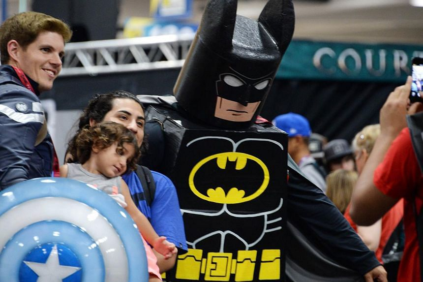 A mother and child pose for a photo with costumed attendees on the first day of the 45th annual San Diego Comic-Con, in San Diego California on July 24, 2014. -- PHOTO: AFP