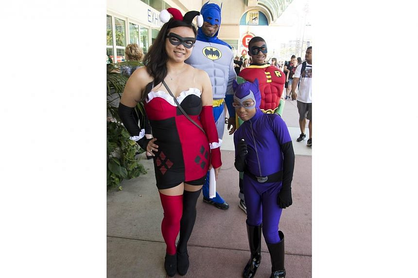 Linda Tran (left) , dressed as Harley Quinn, poses with her boyfriend Erien Hodge (back, left) dressed as Batman and Hodges son Adonis (back, right), 13, and daugther Alexis (right), 8, dressed as Cat Woman, on the first day of the 45th annual San Di