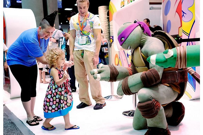 Two year old Ellie Campbell, along with her aunt Jen Pike of Austin, Texas, gets a high-five from the Teenage Mutant Ninja Turtle character Donatello during the 45th annual San Diego Comic-Conin San Diego, Californiaon July 24, 2014. -- P