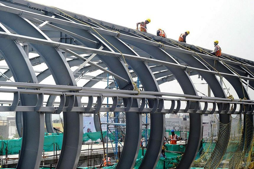 A file picture of Indian Hyderabad Metro Rail (HMR) labourers work at a construction site in Hyderabad. India's new right-wing government under Prime Minister Narendra Modi has promised a new era of greater opportunities andstable and simple ta