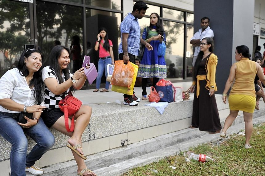 Foreign workers at City Plaza in Paya Lebar, a popular hang-out for Indonesians working here. Sending money home will soon be as easy as sending a text message for the 180,000 Indonesians living in Singapore.-- PHOTO: ST FILE