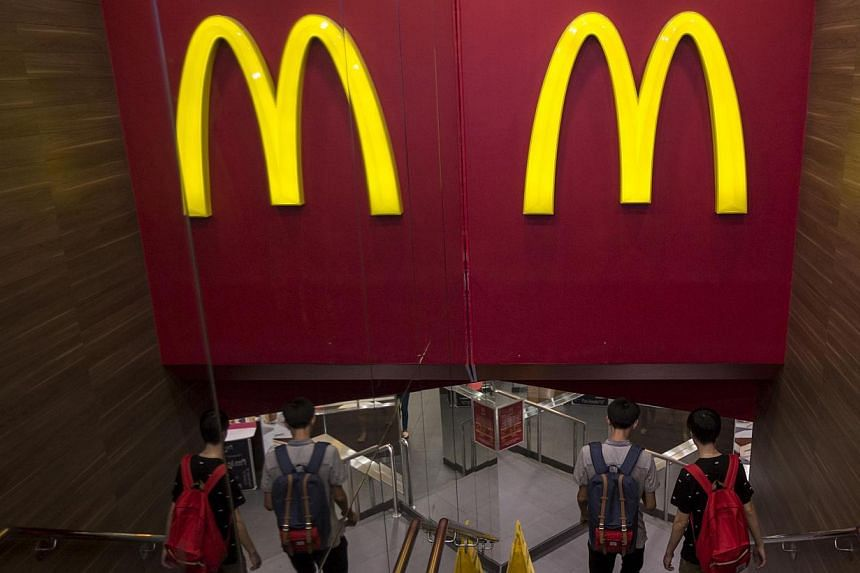 Customers walk into a McDonald's store in Hong Kong on July 25, 2014. McDonald's Hong Kong has suspended sales of chicken nuggets and several other items after admitting it imported food from a US-owned firm in China at the centre of an expired meat