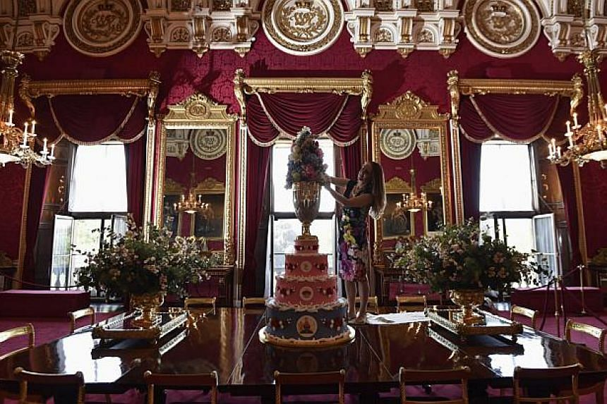 Curator of Royal Collection Trust, Ms Anna Reynolds, adjusts a four-tier Christening cake replicating that made for Queen Victoria's eighth child Prince Leopold in 1853, at Buckingham Palace - the official residence of Britain's Queen Elizabeth - in