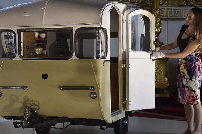 Curator of Royal Collection Trust, Ms Anna Reynolds, poses with a miniature caravan presented by the Caravan Club to Prince Charles and Princess Anne in 1955 at Buckingham Palace - the official residence of Britain's Queen Elizabeth - in central Lond