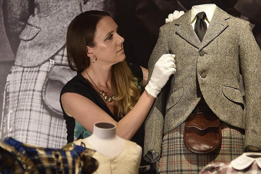 Curator of Royal Collection Trust< Ms Anna Reynolds, poses with a kilt and jacket belonging to Prince Charles from 1958 at Buckingham Palace - the official residence of Britain's Queen Elizabeth - in central London on July 24, 2014. -- PHOTO: REUT