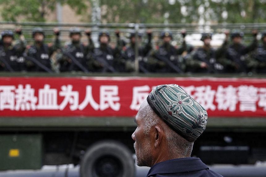 A Uighur man looks on as a truck carrying paramilitary policemen travels along a street during an anti-terrorism oath-taking rally in Urumqi, Xinjiang Uighur Autonomous Region on May 23, 2014.-- PHOTO: REUTERS