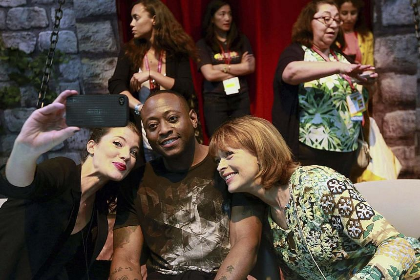 "Actors from TV series Resurrection Devin Kelly (left), Omar Epps (centre) and Frances Fisher take a ""selfie"" before an autograph signing session at the ABC Castle booth, during the 2014 Comic-Con International Convention in San Diego, California on J"