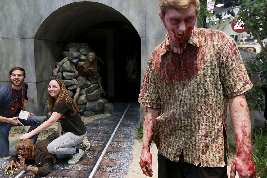 Lyndsay and Don Smith have their photo taken next to a man dressed as a zombie at a booth for The Walking Dead during the 2014 Comic-Con International Convention in San Diego, California on July 25, 2014. -- PHOTO: REUTERS