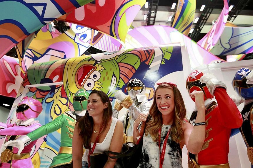 Attendees have their photo taken next to people dressed as the Power Rangers during the 2014 Comic-Con International Convention in San Diego, California on July 25, 2014. -- PHOTO: REUTERS