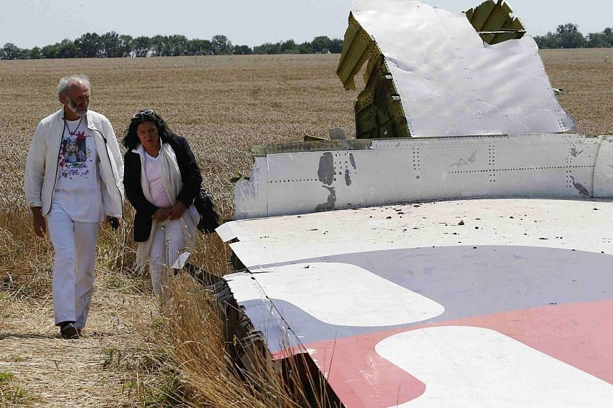 George and Angela Dyczynski walk near wreckage of the downed Malaysia Airlines Flight MH17, during their visit to the crash site near the village of Hrabove (Grabovo), in Donetsk region on July 26, 2014. -- PHOTO: REUTERS