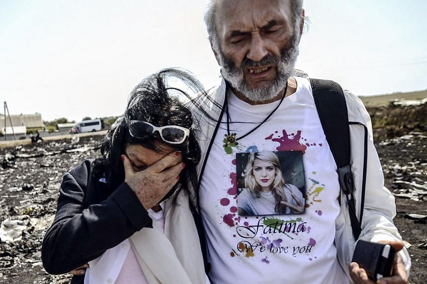Jerzy Dyczynski (right) and Angela Rudhart-Dyczynski from Australia react as they arrive on July 26, 2014 at the crash site of the Malaysia Airlines Flight MH17 to look for their late daughter Fatima, near the village of Hrabove (Grabovo), in the Don
