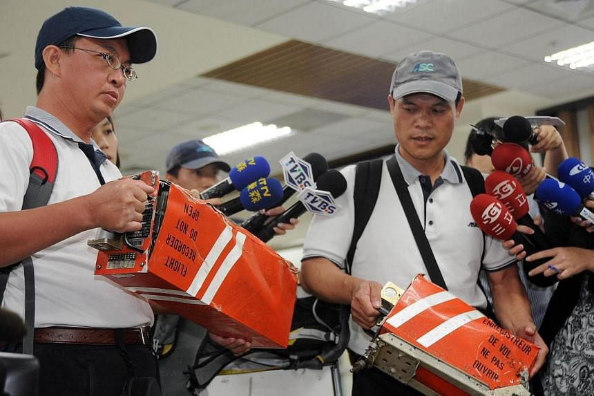 Two members of Aviation Safety Council hold the two black boxes from TransAsia Airways flight GE222 that crashed in the Penghu island chain, in Taipei on July 25, 2014.International experts were examining the site of the fatal TransAsia Airways