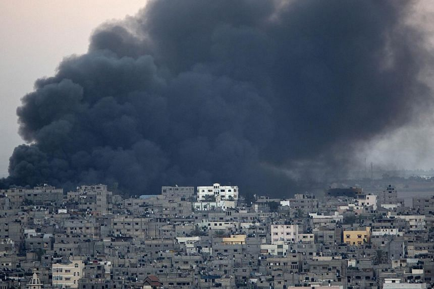 Smoke billows from a building hit by an Israeli air strike in Gaza City on July 25, 2014.The Israeli military and Hamas said on Saturday that they would observe a 12-hour ceasefire from 8:00 am (1:00pm Singapore time), but a longer-term truce r